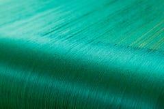 Πράσινο μετάξι σε έναν στρεβλώνοντας αργαλειό ενός υφαντικού μύλου Στοκ φωτογραφία με δικαίωμα ελεύθερης χρήσης