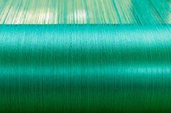 Πράσινο μετάξι σε έναν στρεβλώνοντας αργαλειό ενός υφαντικού μύλου Στοκ Φωτογραφία