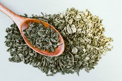 Πράσινο ξηρό τσάι και ξύλινο κουτάλι στοκ φωτογραφία με δικαίωμα ελεύθερης χρήσης