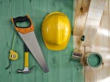 Πράσινο ξύλινο πάτωμα με μια βούρτσα, ένα χρώμα, ένα πριόνι, ένα σφυρί και ένα κράνος Στοκ φωτογραφία με δικαίωμα ελεύθερης χρήσης