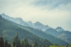 Πράσινο ξύλο βουνά ενός στα himalayan χιονιού υποβάθρου και τα άσπρα σύννεφα Στοκ Φωτογραφία