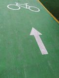 Πράσινο πάτωμα παρόδων ποδηλάτων που χρωματίζεται με το άσπρο χρώμα του συμβόλου βελών και ποδηλάτων Στοκ Εικόνα
