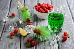 Πράσινο παγωτό Popsicle με τον ασβέστη και το σμέουρο Στοκ Φωτογραφία