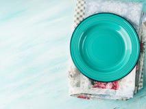 Πράσινο πιάτο στο εκλεκτής ποιότητας ξύλινο κατασκευασμένο υπόβαθρο πετσετών Στοκ Εικόνα
