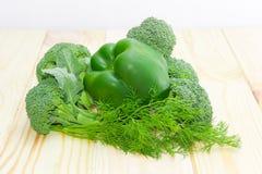 Πράσινο πιπέρι κουδουνιών μεταξύ των κλάδων του μπρόκολου και του άνηθου Στοκ Φωτογραφίες