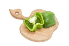 Πράσινο πιπέρι κουδουνιών, περικοπή στο μισό σε έναν τέμνοντα πίνακα Στοκ Εικόνες