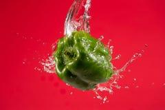 Πράσινο πιπέρι στο κόκκινο υπόβαθρο Στοκ φωτογραφία με δικαίωμα ελεύθερης χρήσης
