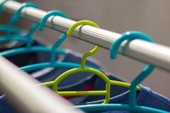 Πράσινο πλαστικό κρεμαστρών στη σειρά ενδυμάτων με μια μπλε κρεμάστρα Pla στοκ εικόνες με δικαίωμα ελεύθερης χρήσης