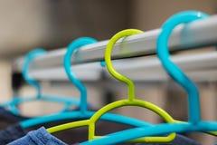 Πράσινο πλαστικό κρεμαστρών στη σειρά ενδυμάτων με μια μπλε κρεμάστρα Pla στοκ φωτογραφίες