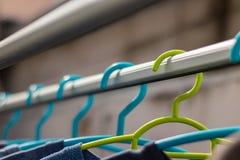 Πράσινο πλαστικό κρεμαστρών στη σειρά ενδυμάτων με μια μπλε κρεμάστρα Pla στοκ φωτογραφία με δικαίωμα ελεύθερης χρήσης