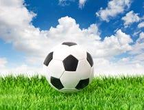 Πράσινο ποδόσφαιρο υποβάθρου μπλε ουρανού χλόης σφαιρών ποδοσφαίρου Στοκ Εικόνα