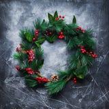 Πράσινο στεφάνι Χριστουγέννων στο σκοτεινό ξύλινο τρύγο Στοκ Εικόνες