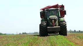 Πράσινο τρακτέρ με το κόκκινο βαγόνι εμπορευμάτων φορτωτών στον τομέα σιταριού και έναν σαφή μπλε ουρανό r απόθεμα βίντεο