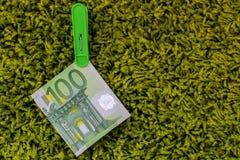 Πράσινο τραπεζογραμμάτιο 100 ευρώ σε έναν πράσινο γόμφο ενδυμάτων στο πράσινο υπόβαθρο Στοκ Εικόνα