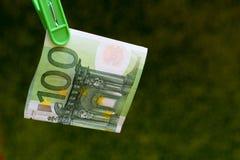 Πράσινο τραπεζογραμμάτιο 100 ευρώ σε έναν πράσινο γόμφο ενδυμάτων στο πράσινο υπόβαθρο στοκ εικόνες