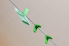 Πράσινο τραπεζογραμμάτιο 100 ευρώ σε έναν πράσινο γόμφο ενδυμάτων Στοκ Φωτογραφίες