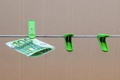 Πράσινο τραπεζογραμμάτιο 100 ευρώ στον πράσινο γόμφο ενδυμάτων Στοκ φωτογραφία με δικαίωμα ελεύθερης χρήσης