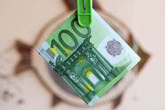 Πράσινο τραπεζογραμμάτιο 100 ευρώ στον πράσινο γόμφο ενδυμάτων Στοκ Εικόνα