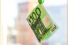 Πράσινο τραπεζογραμμάτιο 100 ευρώ στον πράσινο γόμφο ενδυμάτων Στοκ εικόνες με δικαίωμα ελεύθερης χρήσης