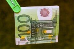 Πράσινο τραπεζογραμμάτιο 100 ευρώ στον πράσινο γόμφο ενδυμάτων στοκ εικόνες