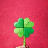 Πράσινο τριφύλλι origami εγγράφου εκμετάλλευσης χεριών Στοκ Φωτογραφία