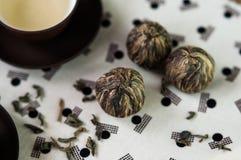 Πράσινο τσάι και μικρή δέσμη σφαιρών των ξηρών πράσινων φύλλων τσαγιού Στοκ εικόνα με δικαίωμα ελεύθερης χρήσης