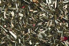 Πράσινο τσάι με τα ρόδινα και κίτρινα πέταλα λουλουδιών ως υπόβαθρο Στοκ φωτογραφίες με δικαίωμα ελεύθερης χρήσης