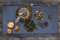 Πράσινο τσάι με το κέικ, τους ξηρούς καρπούς και τη σοκολάτα Στοκ Φωτογραφία
