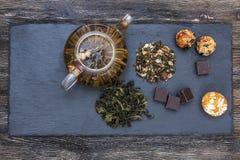 Πράσινο τσάι με το κέικ, τους ξηρούς καρπούς και τη σοκολάτα Στοκ Εικόνα