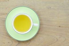 Πράσινο τσάι στο πράσινο φλυτζάνι στον ξύλινο πίνακα Στοκ Εικόνες