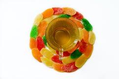 Πράσινο τσάι στο φλυτζάνι γυαλιού με τα γλυκά - γλασαρισμένος ανανάς στο λευκό Στοκ Εικόνες