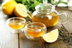 Πράσινο τσάι στο φλυτζάνι και teapot στο καφετί ξύλινο υπόβαθρο Στοκ εικόνες με δικαίωμα ελεύθερης χρήσης