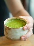 Πράσινο τσάι Matcha στο χέρι γυναικών στοκ εικόνα με δικαίωμα ελεύθερης χρήσης