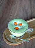 Πράσινο τσάι Matcha latte σε ένα φλυτζάνι γυαλιού σε ένα ξύλινο πιάτο Στοκ Εικόνες
