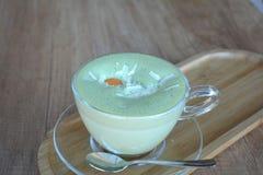 Πράσινο τσάι Matcha latte σε ένα φλυτζάνι γυαλιού σε ένα ξύλινο πιάτο Στοκ Εικόνα