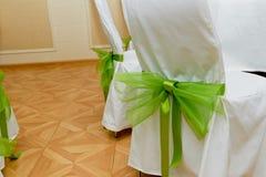 Πράσινο τόξο σε μια καρέκλα γάμος κορδελλών πρόσκλησης λουλουδιών κομψότητας λεπτομέρειας διακοσμήσεων ανασκόπησης Στοκ Φωτογραφίες