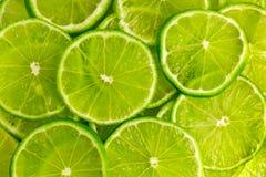 Πράσινο υπόβαθρο με τις φέτες ασβέστη Στοκ Εικόνες