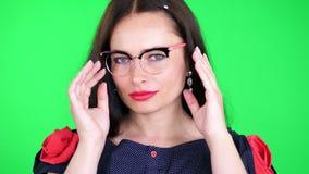 Πράσινο υπόβαθρο, chromeakey πορτρέτο μιας προκλητικής γυναίκας brunette με τα κόκκινα χείλια, στα μοντέρνα γυαλιά, θεάματα, erot απόθεμα βίντεο