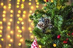 Πράσινο χριστουγεννιάτικο δέντρο που διακοσμούνται με τα παιχνίδια Χριστουγέννων και μια γιρλάντα με τα κίτρινα φω'τα Στοκ Εικόνες