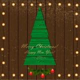 Πράσινο χριστουγεννιάτικο δέντρο στο ξύλινο υπόβαθρο με τη γιρλάντα του λι Στοκ Φωτογραφίες