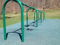 Πράσινο swingset σε ένα πάρκο με το δασικό υπόβαθρο Στοκ εικόνες με δικαίωμα ελεύθερης χρήσης