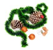 Πράσινο tinsel Χριστουγέννων, σφαίρες Χριστούγεννο-δέντρων, κώνοι πεύκων και cha στοκ φωτογραφίες