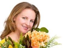 Πραγματικά ευτυχής γυναίκα που χαμογελά πίσω από την ανθοδέσμη λουλουδιών Στοκ Φωτογραφίες