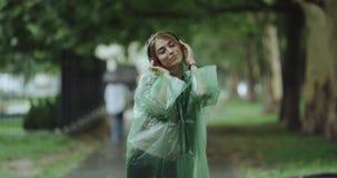 Πραγματικά συγκινήσεις της νέας μουσικής ακούσματος ladie από τα ακουστικά και χορός στη βροχή, χαμόγελο, άνθρωποι υποβάθρου απόθεμα βίντεο