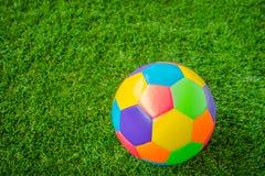 Πραγματική σφαίρα ποδοσφαίρου χρώματος δέρματος ζωηρόχρωμη πολυ στην πράσινη χλόη στοκ φωτογραφία με δικαίωμα ελεύθερης χρήσης