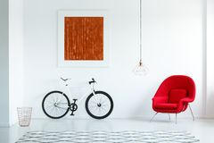 Πραγματική φωτογραφία ενός ποδηλάτου με τις μαύρες ρόδες, κόκκινη πολυθρόνα, ζωγραφική Στοκ Εικόνες