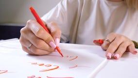 Πρακτικές σπουδαστών καλλιγράφων στο γράψιμο της ΑΓΑΠΗΣ λέξης με τον κόκκινο δείκτη στον καμβά Δημιουργικός καλλιτέχνης freelance απόθεμα βίντεο