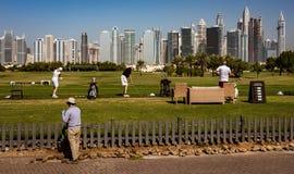 Πρακτική παικτών γκολφ στην οδήγηση της σειράς με τον ορίζοντα του Ντουμπάι στην πλάτη Στοκ εικόνες με δικαίωμα ελεύθερης χρήσης