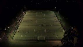 Πρακτική ποδοσφαίρου σε μια πίσσα Floodlit Astroturf απόθεμα βίντεο