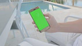 ΠΡΑΣΙΝΟ άτομο ΟΘΟΝΗΣ που κρατά το κινητό τηλέφωνό του φιλμ μικρού μήκους